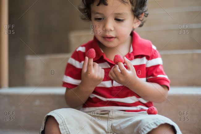 Boy with raspberries on fingers
