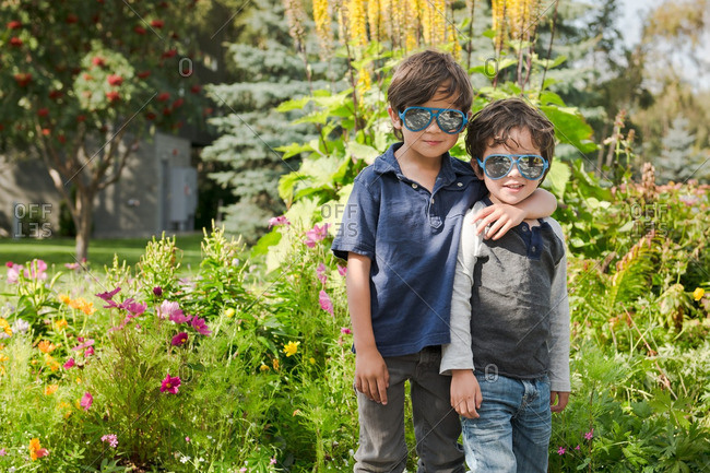 Two boys with sunglasses on outside