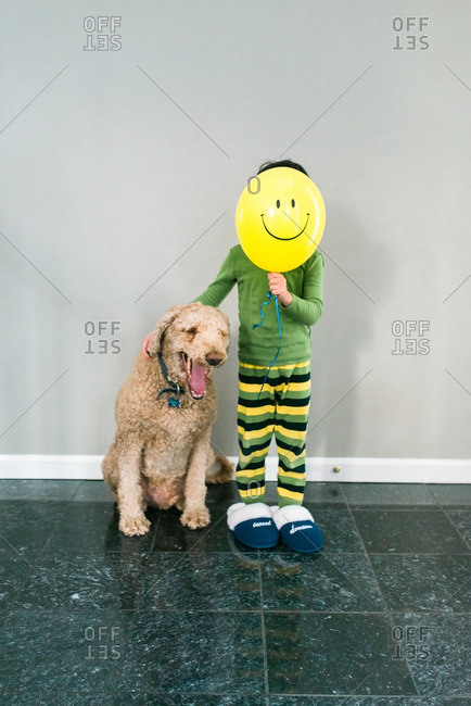 Boy with smiley balloon by dog