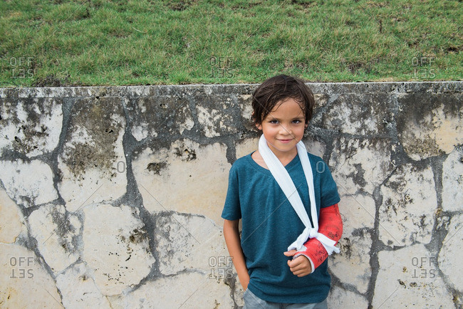 Boy with arm in cast by wall