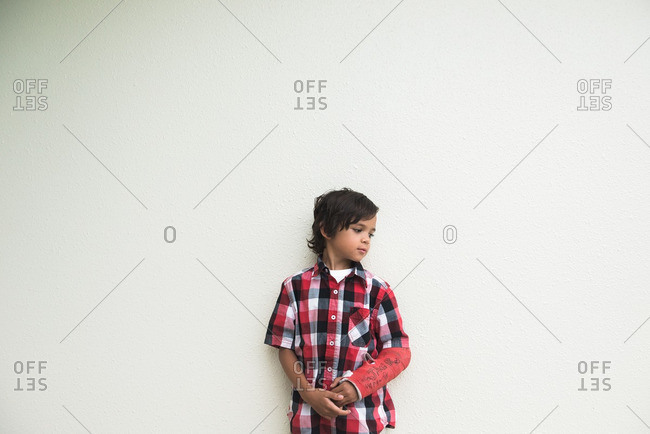 Boy with cast in front of white wall
