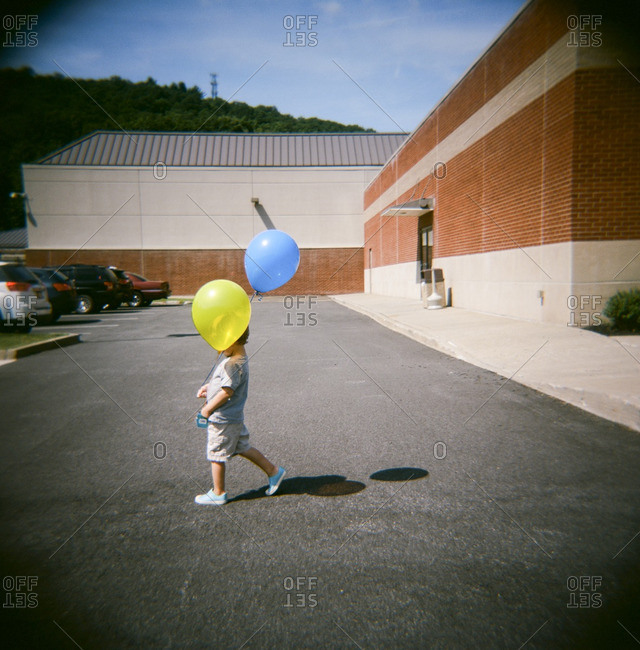 Boy in school parking lot with balloons