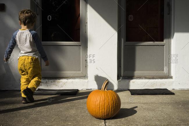 Boy by front door near pumpkin