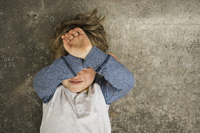 Boy covering face lying on concrete