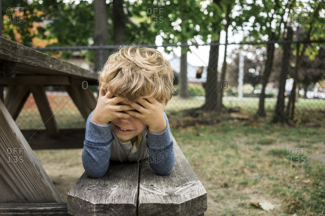 Boy on picnic table bench covering eyes
