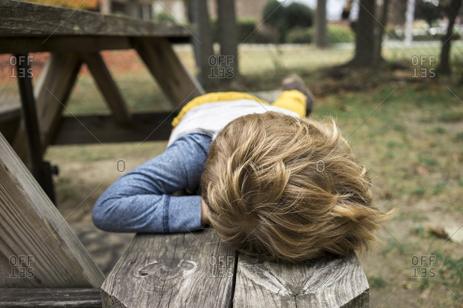 Boy lying on picnic table bench