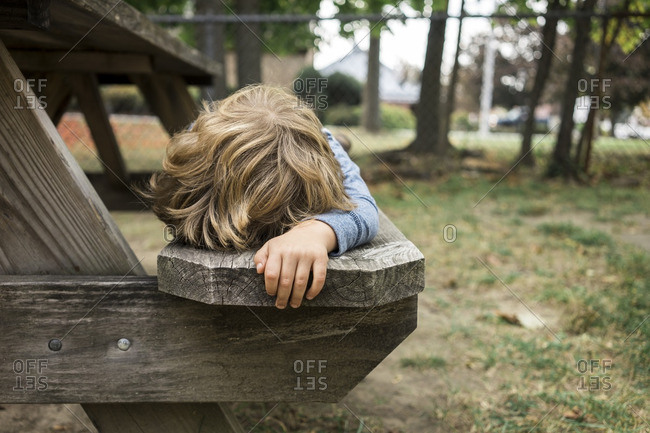 Boy laying on picnic table bench