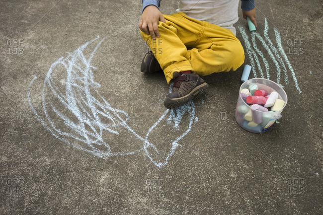 Boy doodling with sidewalk chalk