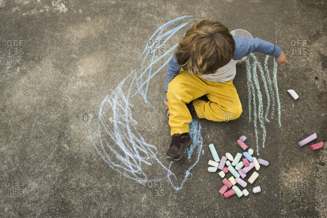 Boy sitting doodling with sidewalk chalk