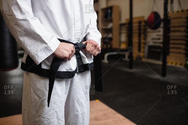 Mid-section of man practicing karate in fitness studio