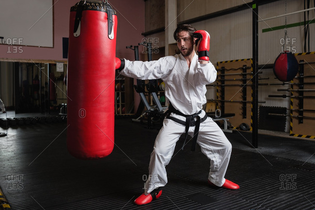 Man practicing karate with punching bag in fitness studio