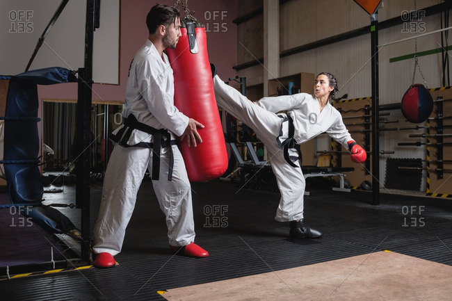 Man and woman practicing karate with punching bag in studio