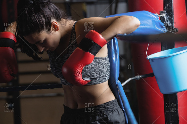 Female boxer taking a break after a practice in fitness studio