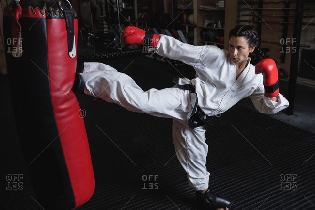 Woman practicing karate with punching bag in fitness studio