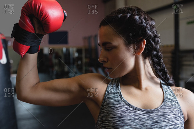 Female boxer in boxing gloves showing muscle in fitness studio