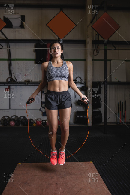 Woman exercising with skipping rope in fitness studio