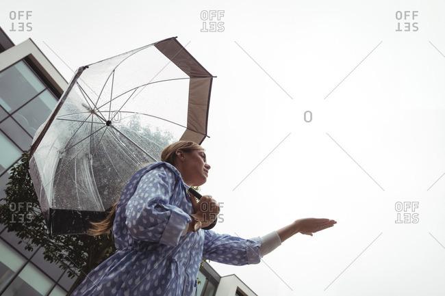 Low angle view of beautiful woman enjoying rain during rainy season