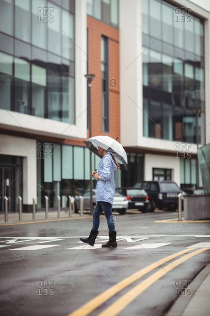 Woman holding umbrella and crossing street during rainy season