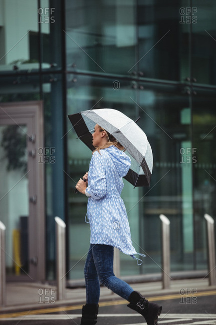 Beautiful woman holding umbrella and walking on street during rainy season