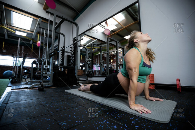 Pregnant woman performing stretching exercise on exercise mat in gym