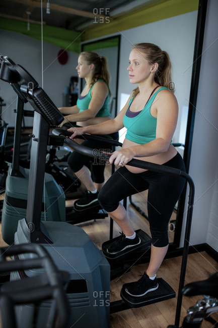 Pregnant woman exercising on elliptical machine at gym