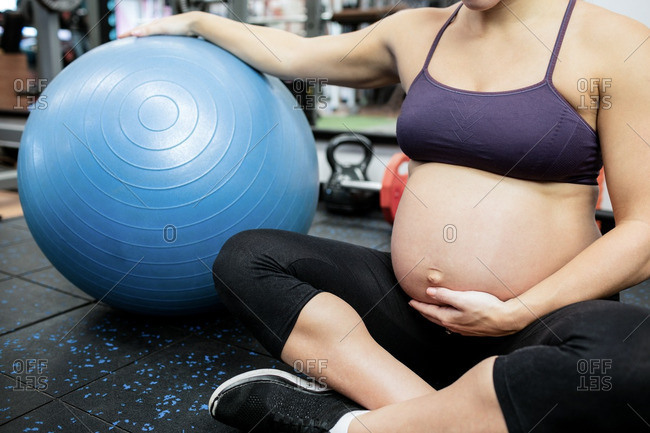 Pregnant woman holding her belly in gym