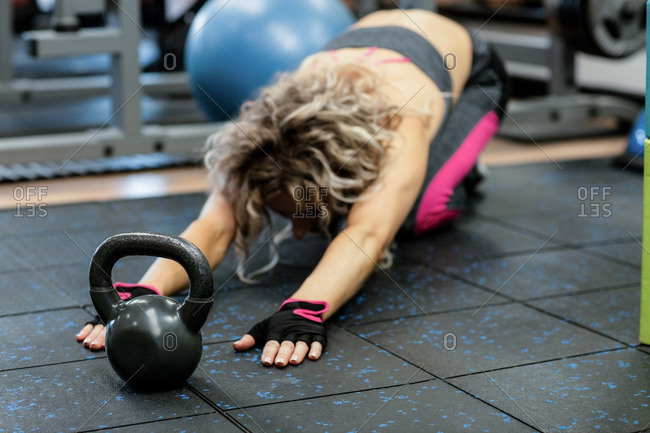 Woman performing stretching exercise with kettlebell in gym