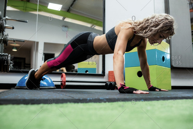 Woman performing push-up exercise in gym