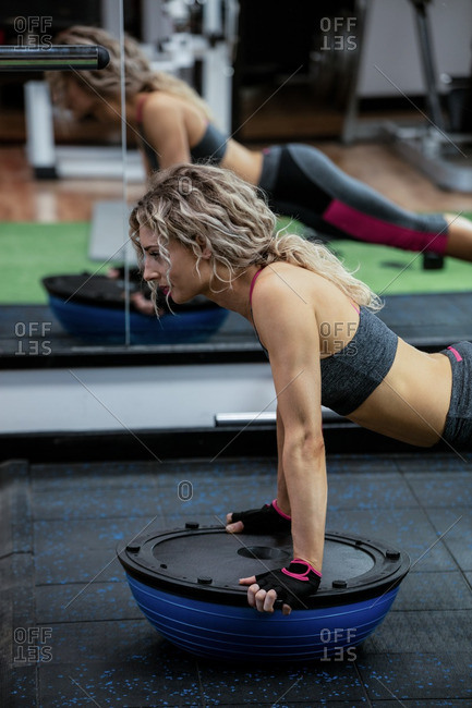 Woman doing push-up on balance ball in gym