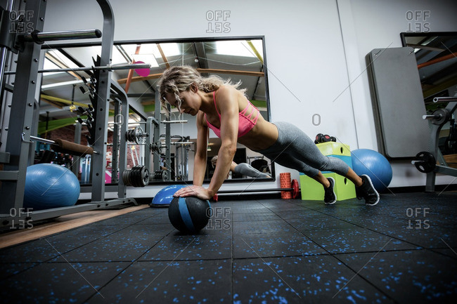 Woman doing push-up on exercise ball in gym