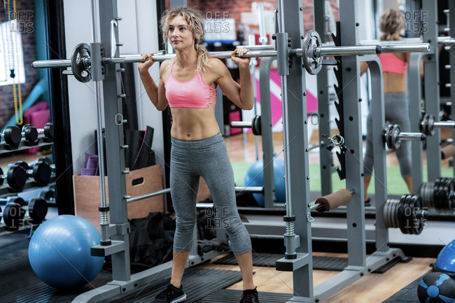 Beautiful woman working out with barbell at gym