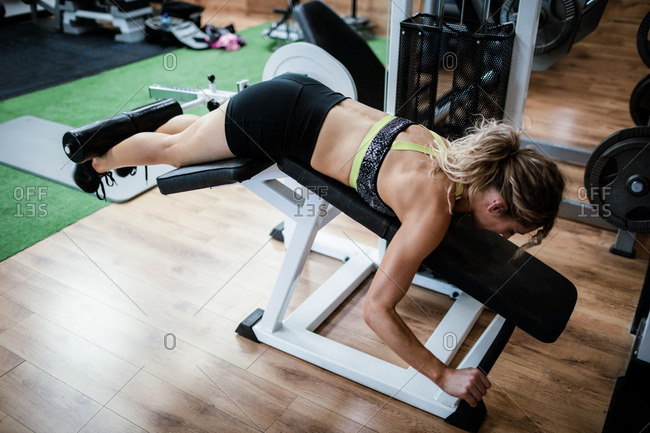 Woman performing exercise on bench press in gym