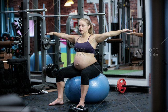 Pregnant woman preforming stretching exercise on fitness ball in gym
