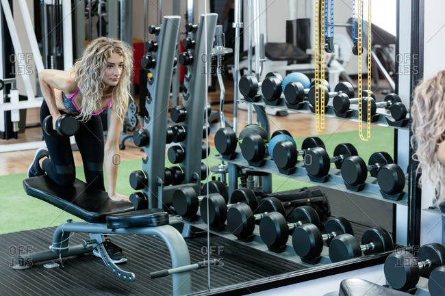Woman lifting dumbbells at gym
