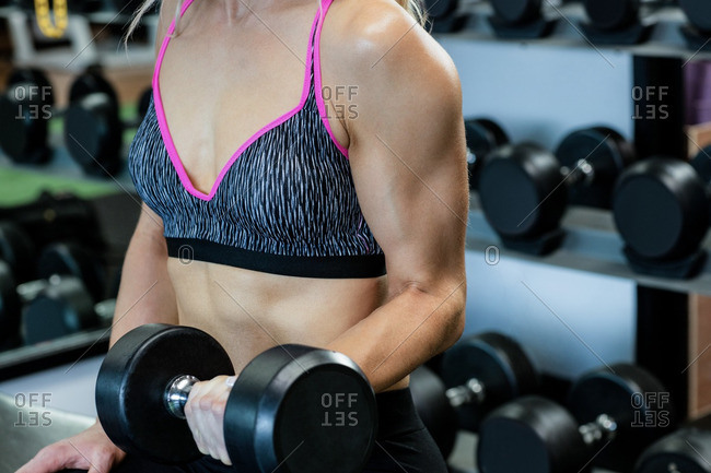 Mid-section of woman lifting dumbbells at gym