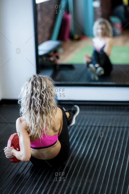 Rear view of woman working out in gym