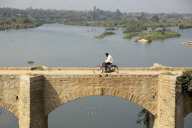 India - October 21, 2016: Man cycling on a brick bridge