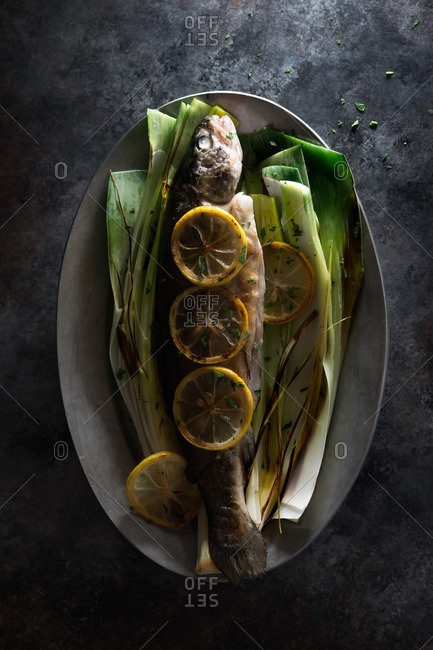Fried trout served with grilled leeks and lemon slices