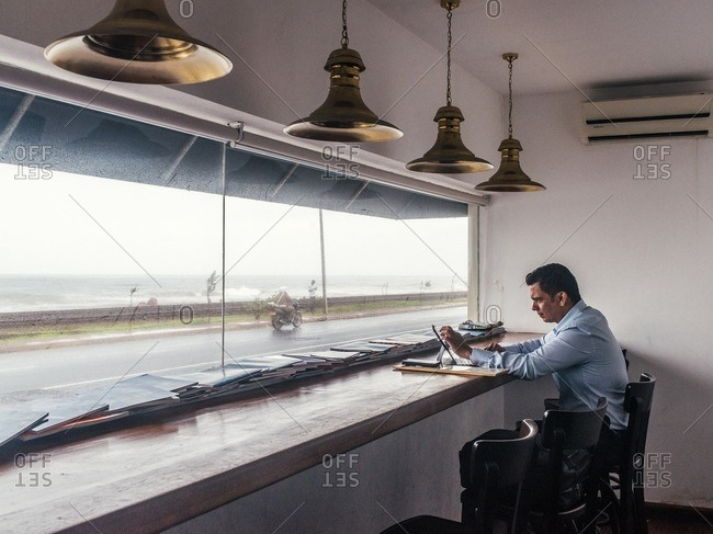 Colombo, Sri Lanka - June 10, 2016: Man using computer a table overlooking the sea at Wright & Co. cafe in Colombo, Sri Lanka