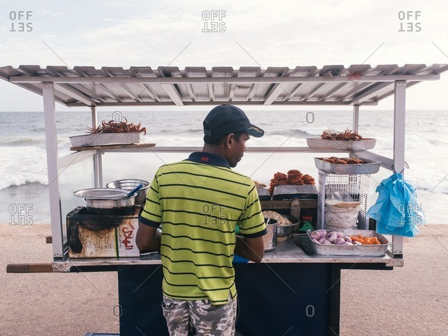 Colombo, Sri Lanka - June 10, 2016: A vendor making a type of shrimp-topped pancakes on Galle Face Green, Colombo, Sri Lanka