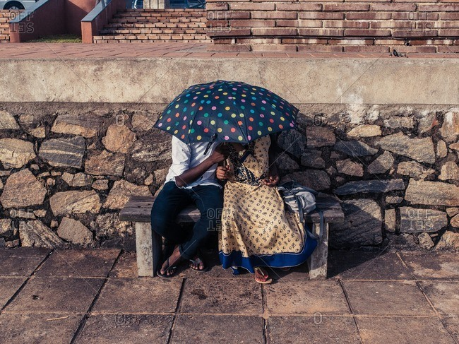 Colombo, Sri Lanka - June 10, 2016: A couple huddled close underneath an umbrella on Galle Face Green, Sri Lanka