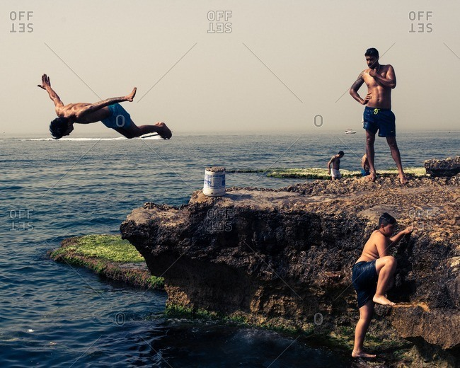Beirut, Lebanon - May 14, 2016: Young men jumping off a cliff on the coast of Beirut, Lebanon