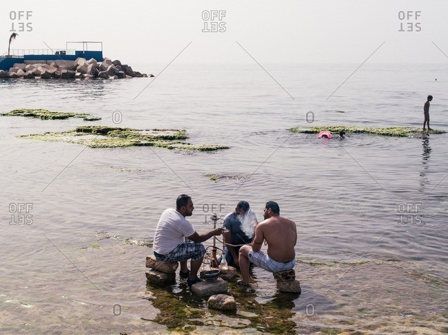 Beirut, Lebanon - May 14, 2016: Man smoking hookah pipe in the sea