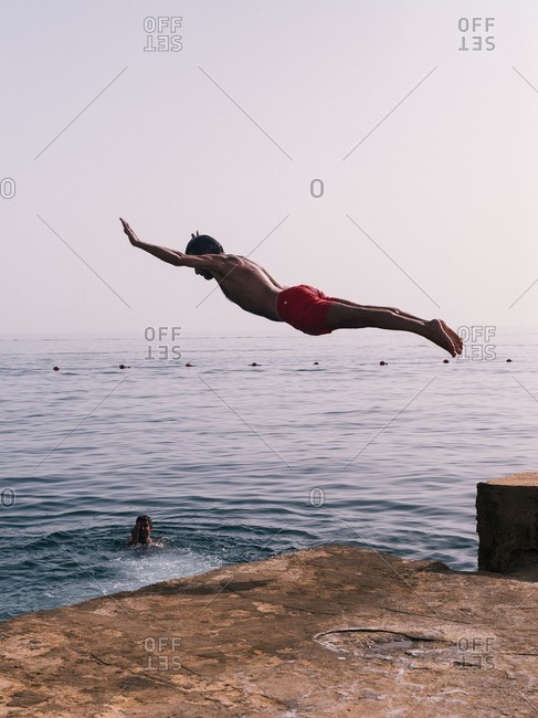 Beirut, Lebanon - May 14, 2016: Young man jumping off the coast of Beirut, Lebanon