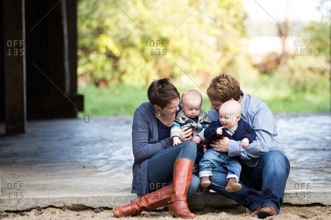 Women holding their twin babies outdoors