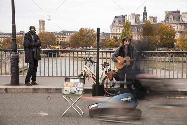 Paris, France - November 11, 2014: Musician performing on bridge over the river Seine