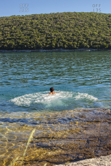 Young man swimming in the Adriatic Sea in Croatia