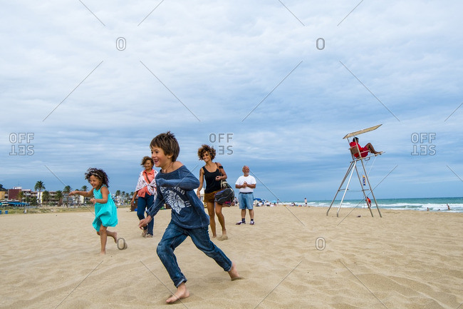 Barcelona, Spain - July 30, 2015: Children running on a beach in Castelldefels