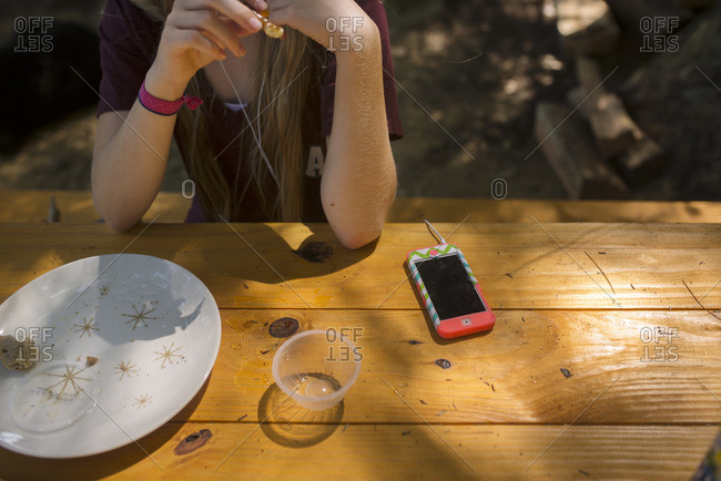 Tween girl listening to music on her cell phone will eating lunch on a picnic table