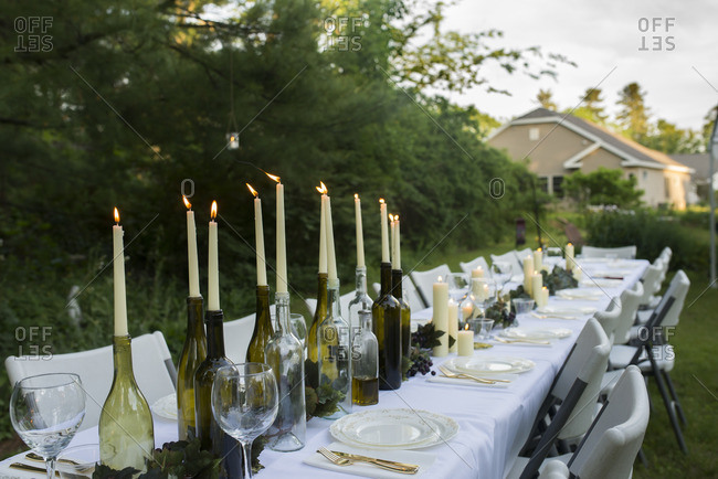 Outdoor dinner table set with candles in wine bottles